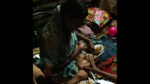 Mère et son enfant, dans le bidonville de Out Fall, dans le quartier de Kamalapour à Dhaka.